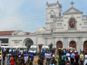 Ambulances are seen outside the church premises with gathered people and security personnel following a blast at the St. Anthony's Shrine in Kochchikade, Colombo on April 21, 2019. - Explosions have hit three churches and three hotels in and around the Sri Lankan capital of Colombo, police said on April 21. (Photo by ISHARA S.  KODIKARA / AFP)