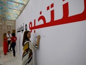Des Tunisiens écrivent et signent un grand panneau sur lequel est inscrit : «Nous élisons et nous continuons», lors de l'ouverture de la salle de presse pour l'élection présidentielle, le 12 septembre à Tunis. © REUTERS/Muhammad Hamed